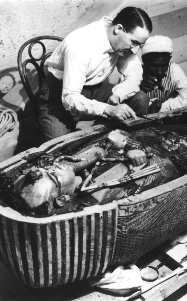 Howard Carter, an English archaeologist, examining the opened sarcophagus of King Tut.