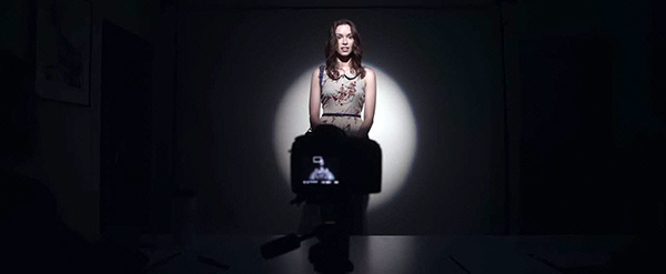 At the second audition, things are very different. She enters a dark room with a spotlight pointed at her.