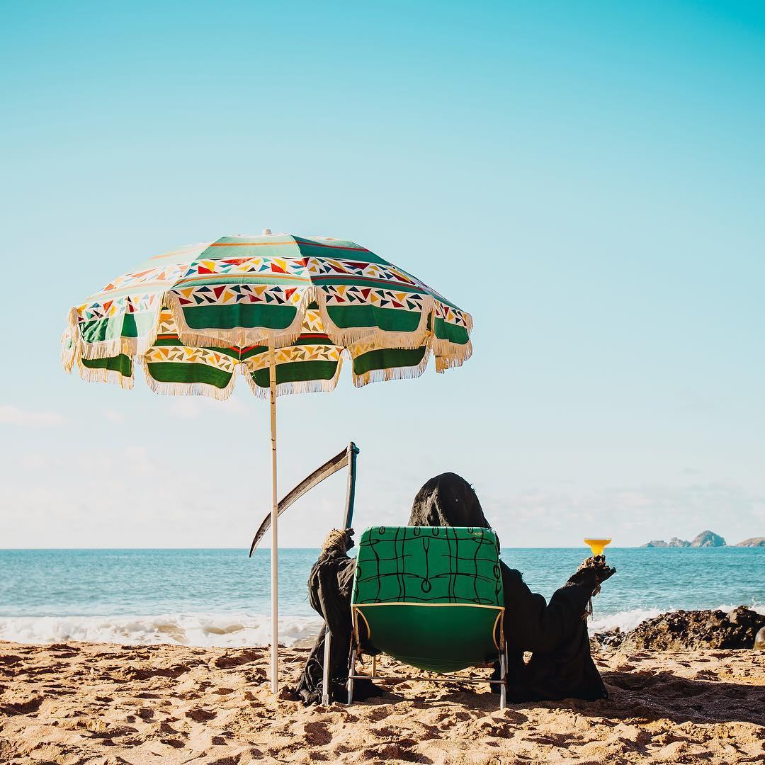 Death enjoys a drink on the beach