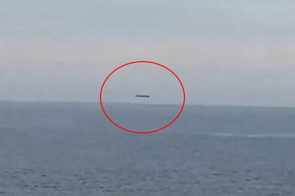 A huge cylindrical UFO is filmed over the Welsh sea 91