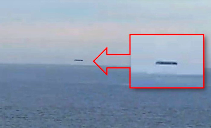 A huge cylindrical UFO is filmed over the Welsh sea 90