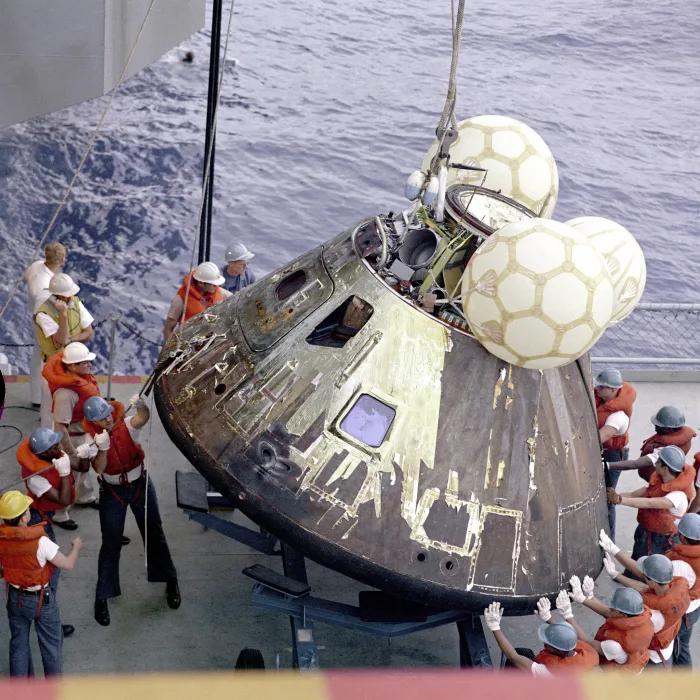 Crew members of USS Iwo Jima, the main rescue ship for the Apollo 13 mission, lift the command module aboard.  NASA
