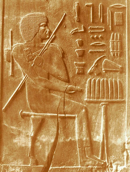 "The architect of the restoration of the pyramid under the Pharaoh Cheops Khesi-Ra with tools and a ruler - ""elbow"".  A cedar plaque depicting Hesi-Ra from his tomb (photo from the Wikipedia article ""Hesyra"", Author: Hesy-Ra_CG1426.jpg: User: GDK: James Edward Quibell († 5. Juni 1935) derivative work: JMCC1 (talk) - Hesy -Ra_CG1426.jpg, Public domain, https://commons.wikimedia.org/w/index.php?curid=15484621)"