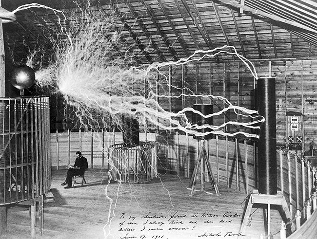 Tesla in front of a high frequency transformer at the Colorado Springs lab.